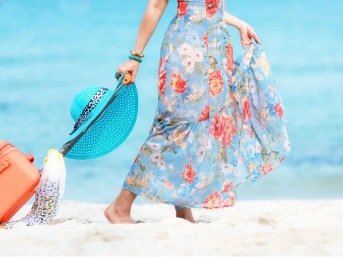 リゾートワンピースで海辺を歩く女性の写真