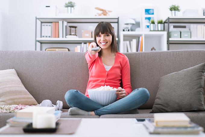 ソファでお菓子を食べテレビを見る女性
