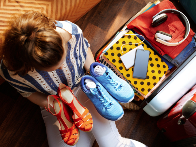 靴とサンダルをキャリーケースに収納しようとする女性の写真