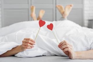 ベッドをともにする男女とハート