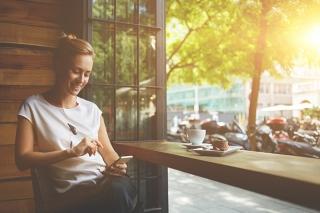 外が見えるカフェの席でひとりお茶する女性