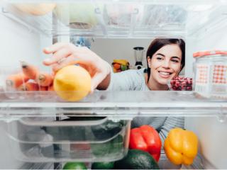 冷蔵庫から食材を取り出す女性の画像