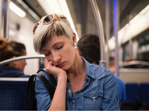 電車の中で疲れて寝ている