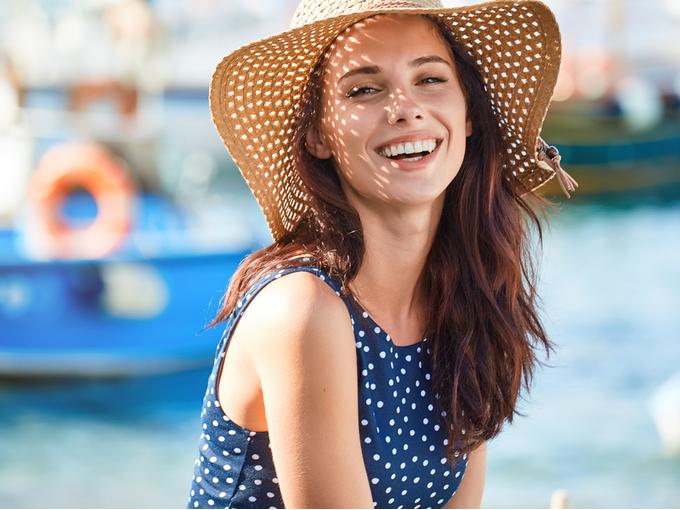 海辺で麦わら帽子をかぶった笑顔の女性