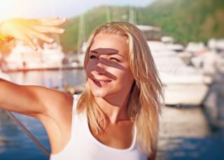 日差しを手で遮っている女性の画像