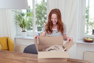 楽しそうに箱を開封している女性のイメージ画像