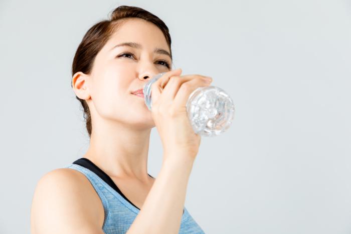 ペットボトルに入った水を飲んでいる女性の画像