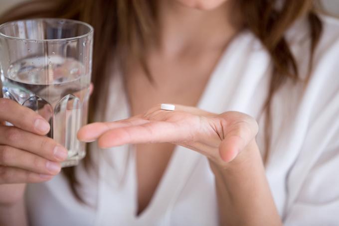 手のひらにある錠剤を水で飲もうとしている画像