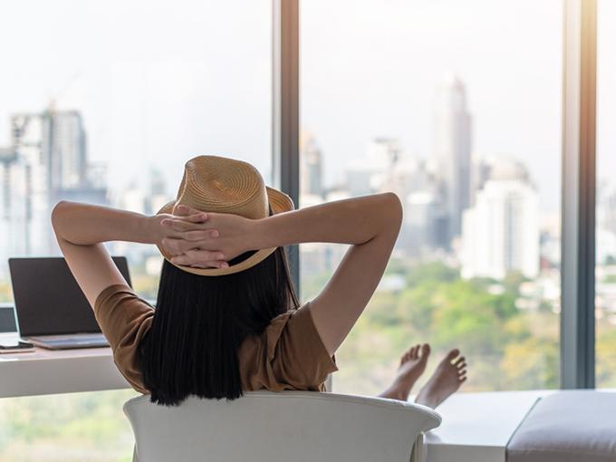 頭の後ろで手を組んで、外を見ている女性の後ろ姿