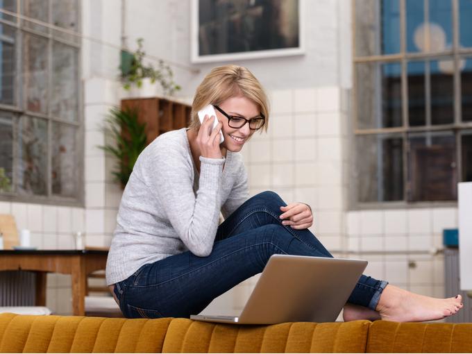 自宅でパソコンを開きながら、仕事の電話をする人