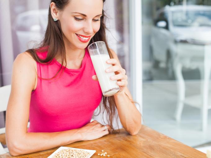 豆乳をコップで飲む女性