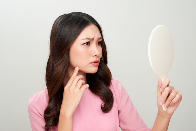 鏡を見て困った表情をしている女性の画像