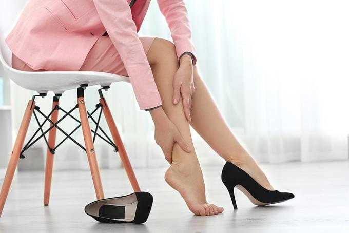 靴を脱いで脚をさする女性の画像