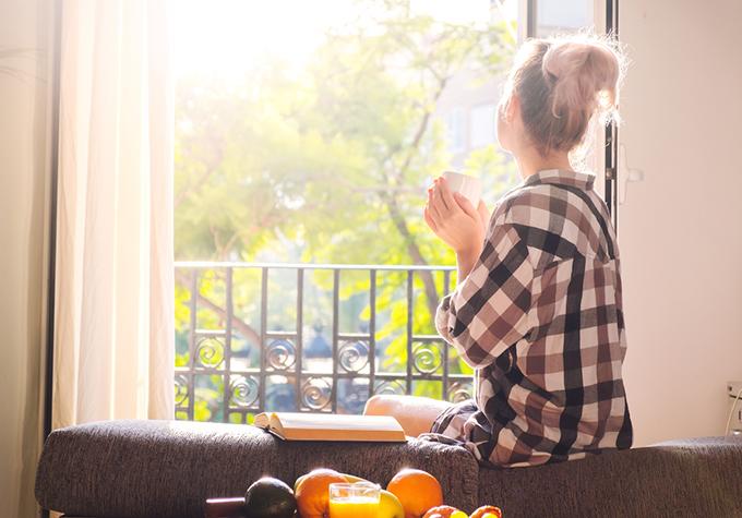 窓から朝日を見ている女性の後ろ姿