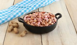 黒い鍋の形をした器にピーナッツがたくさん入っている