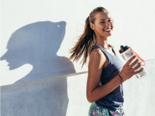 運動中に水のボトルを片手に笑顔の女性