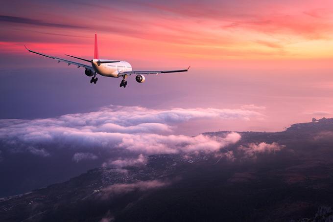 ピンク色の美しい空に飛んでいる飛行機