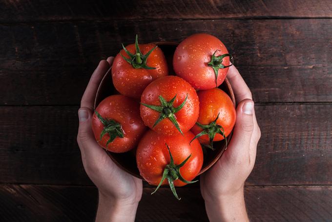 カゴいっぱいに入ったトマトに手を添えている画像