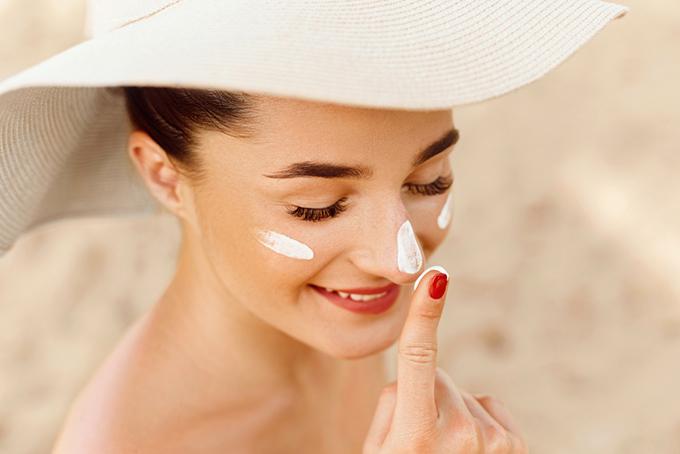日焼け止めを顔に塗っている女性の画像