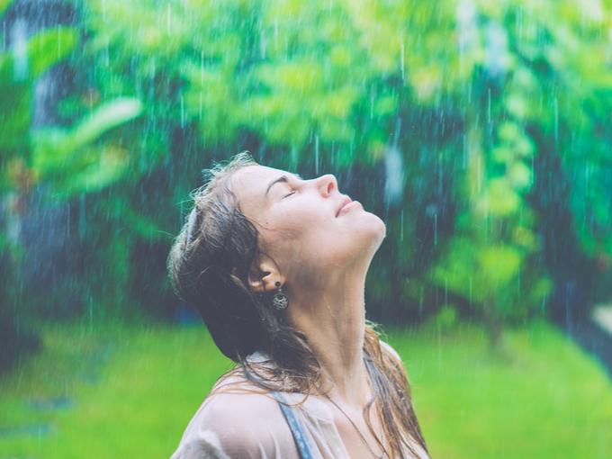 恵みの雨を全身に受ける女性