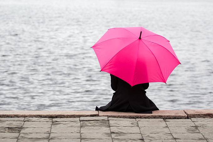 女性が傘をさして海を眺めている写真