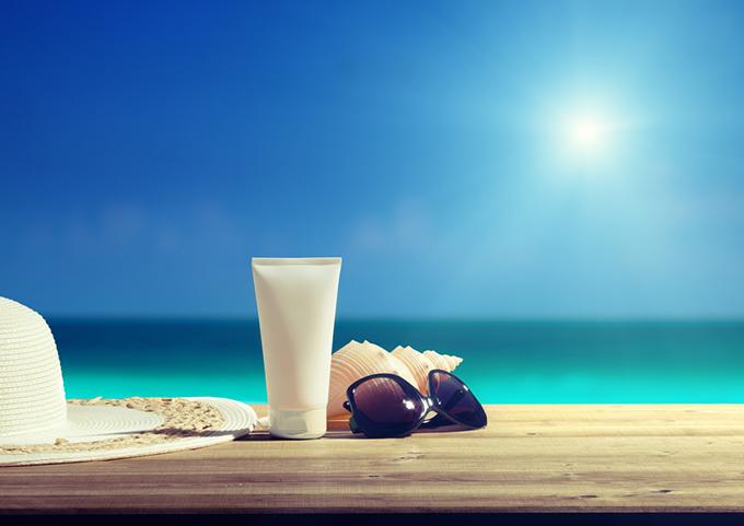 日差しが強い海を背景にクリームとサングラスが置いてある画像