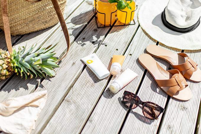 日焼け止めとサングラスや帽子、サンダルなど夏っぽいイメージ画像