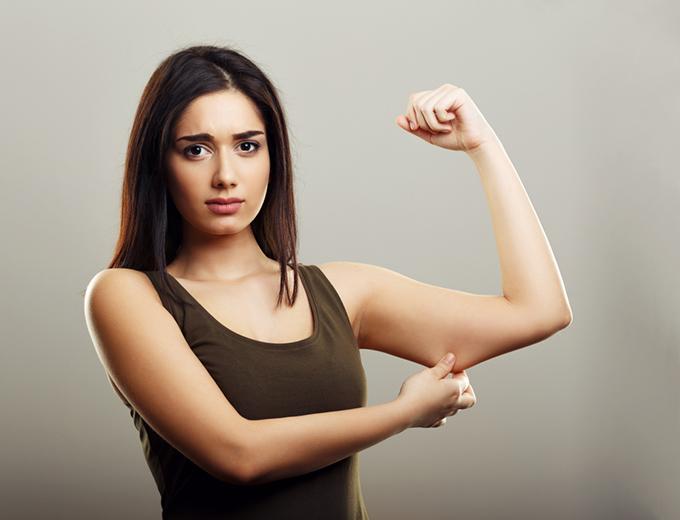二の腕をつまんでいる女性の画像