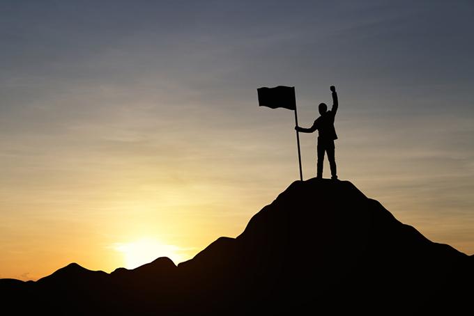 山の頂上で旗を掲げる