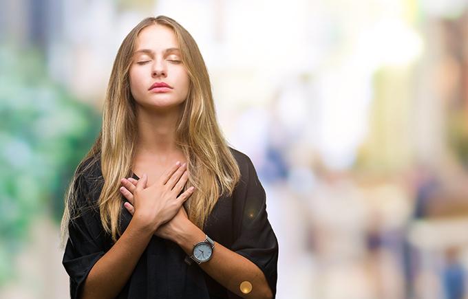 胸に手を当てている女性の写真