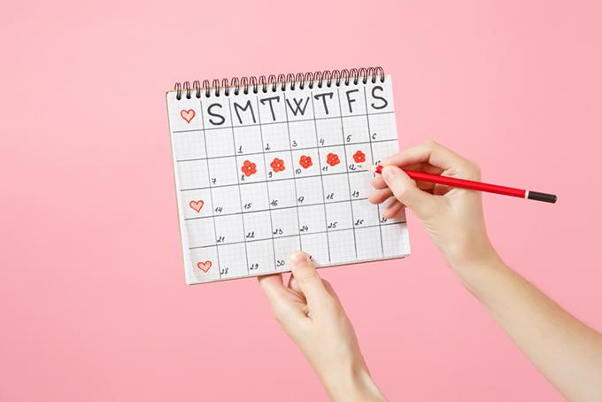 カレンダーに生理日をチェックしている女性の画像