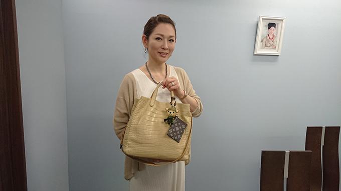 岡江さんがバックを手に持っている写真