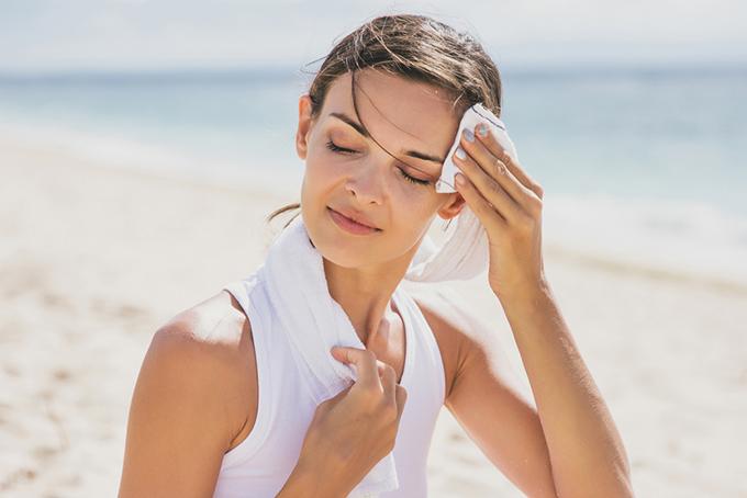 額の汗を拭いているタンクトップ姿の女性の画像