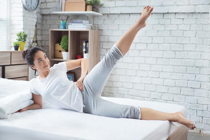 ベットの上、横姿勢で片脚あげている女性のイメージ画像