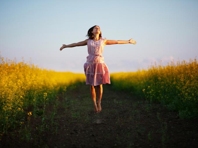 草原で飛び跳ねる女性
