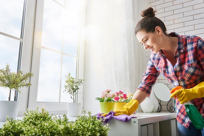 女性が笑顔で掃除をしている写真