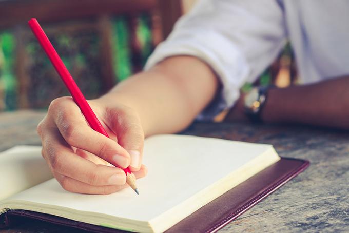 鉛筆を持ってノートに向かっている人の画像