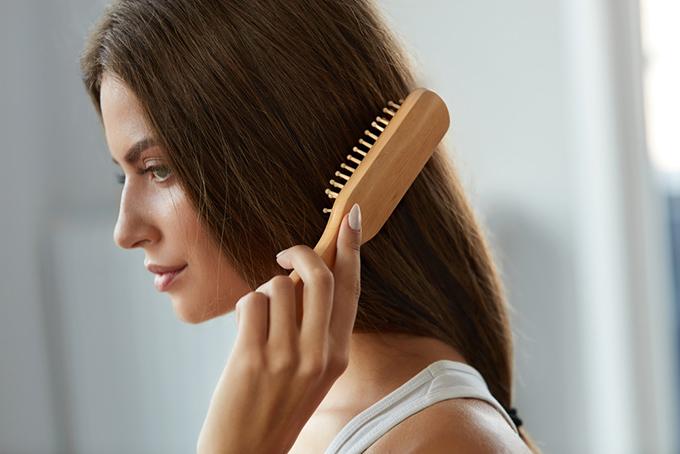 長い髪にブラシをかけている女性の画像