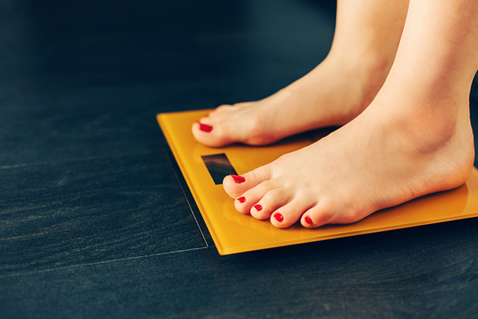 オレンジ色の体重計に乗る女性の足元の画像