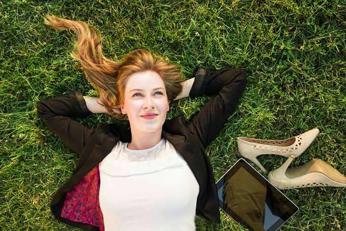 仕事を忘れて芝生の上でリラックスする女性