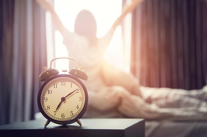 目覚まし時計のアップと目覚めた女性の画像