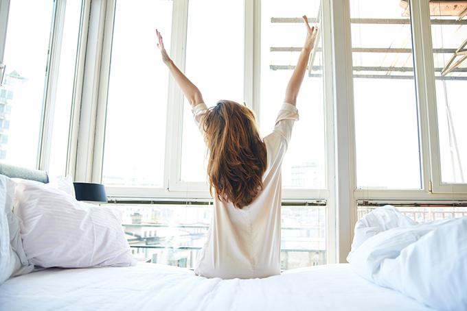 寝起きにバンザイをする女性の画像