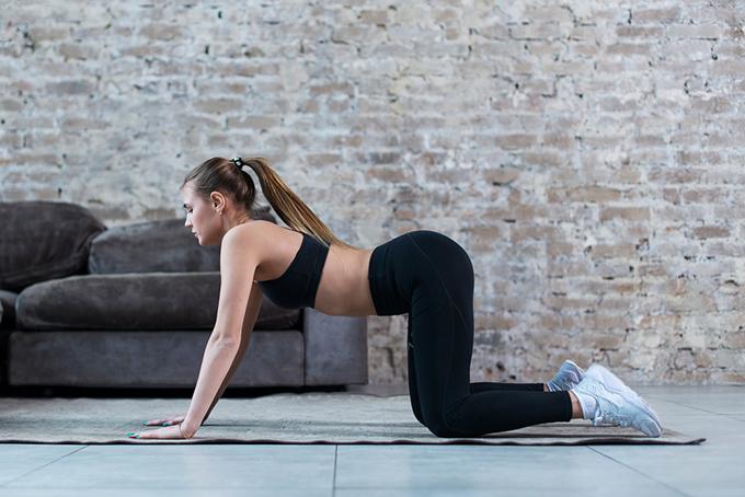 マットの上で両手と膝を床につけている女性の画像