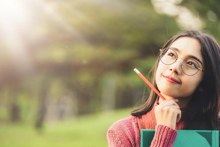 ノートを手に未来を空想する女性