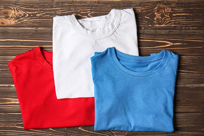 赤・白・青色のTシャツが置いてある画像
