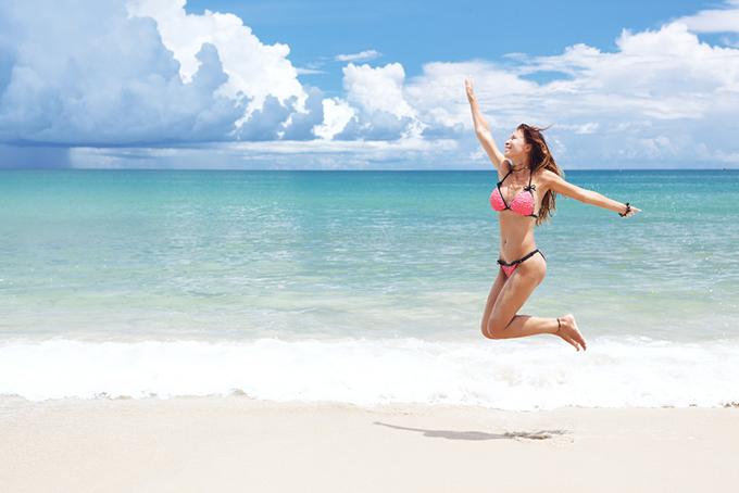 キレイな海でジャンプしている水着姿の女性