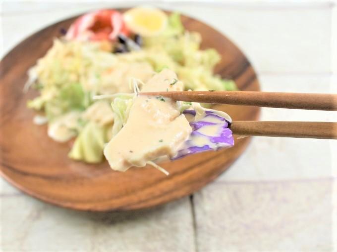 箸で持った「1食分のプロテインサラダ(コブドレッシング)」の画像