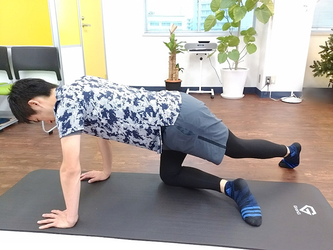 床にマットを敷いて両ひざと両手をつき、左脚を右にクロス