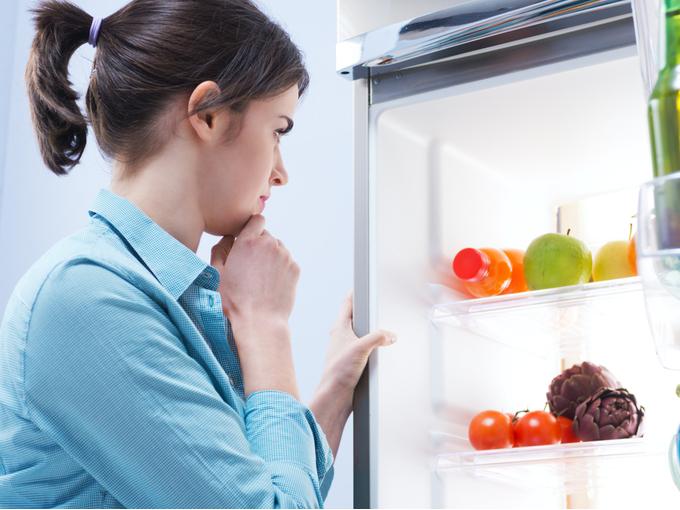 冷蔵庫の前で悩む女性