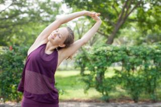 腕を上げて伸びをしている女性の画像